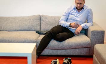 guy sitting on sofa looking at phone