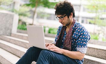 sitter och skriver på datorn