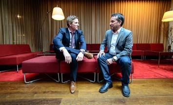 två män pratar på soffan